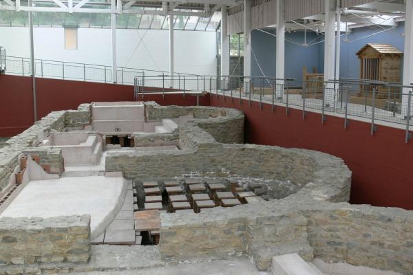 Der Altbau des Museums ist ein Schutzbau über den ausgegrabenen und konservierten Resten des kleineren Bades im Kastellort. Die Originalmauern sind Teil des UNESCO-Welterbes.